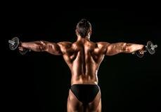 Back muscles. Beautiful muscular man bodybuilder posing back over dark background Stock Photo