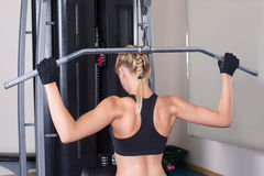 Back muscles exercise by athletic woman Stock Photos