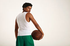 Back of a muscular black athlete holding leather basketball royalty free stock photography