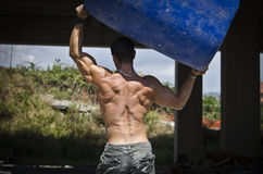 Back of muscular construction worker shirtless. Muscular construction worker shirtless in building site holding big blue barrel over his head, shot from the back Stock Photo
