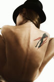 Back of naked suntanned woman. Back of naked suntanned young woman dressed in a black hat royalty free stock photo