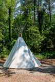 Back on a Native American teepee in a clearing in the woods. A Native American teepee in a wooded clearing stock photo