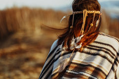 Back of native indian american woman walking in mountains in eve. Ning, hair with feathers stock photos