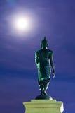 Back Of Walking Buddha Statue In Twilight Stock Photo