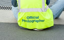 The back of an official photographer sitting, photographing an event royalty free stock photo
