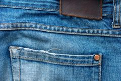 Back of old blue jeans with pocket and a leather tag. Close-up photo royalty free stock image