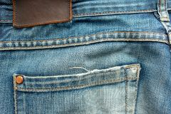 Back of old blue jeans with pocket and a leather tag. Close-up photo stock photo