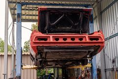 Back Of Old Car On A Hoist. Back of an old car on a hoist being restored in a garage stock image