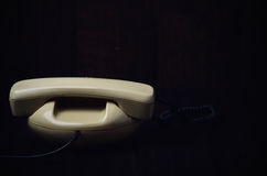 Back of old-fashioned phone on a dark wooden background. horizon Stock Photo