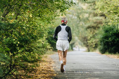 Back oldest male runner running in autumn Park Royalty Free Stock Photography