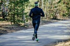 Back one runner male. Running marathon on asphalt road in spring Royalty Free Stock Photo