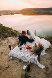 The back outdoor view of the newlyweds touches noses behind the picnic set near the river. Royalty Free Stock Photo
