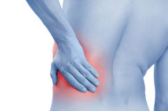 Back-pain. Closeup studio shot of man holding his back with hand having pain Stock Photo
