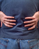 Back Pain. Closeup view of a man holding his back in pain Stock Images