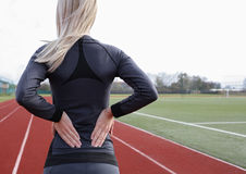 Back Pain. Athletic fitness woman rubbing the muscles of her lower back. Sports exercising injury. Stock Image