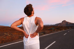 Back pain - Athletic running man with injury. Back pain. Athletic running man with injury in sportswear rubbing touching lower back muscles standing on road Royalty Free Stock Images