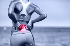 Back pain. Athletic running woman with back injury stock image