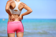 Back pain - Athletic woman rubbing her back. Back pain. Athletic woman in pink sportswear standing at the seaside rubbing the muscles of her lower back, cropped Stock Image