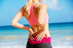 Back Pain Concept. Back Pain. Athletic fitness woman rubbing the muscles of her lower back. Sports exercising injury Stock Images