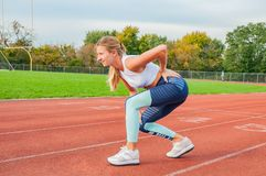 Back pain. Athletic woman on running track touching back with painful injury royalty free stock image