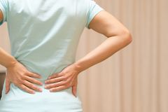 Back pain at home. women suffer from backache. healthcare and medical concept Stock Image