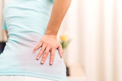 Back pain at home. women suffer from backache. healthcare and medical concept Royalty Free Stock Photos