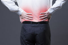 Back pain, kidney inflammation, ache in man`s body. Close-up on gray background with red dot stock photos