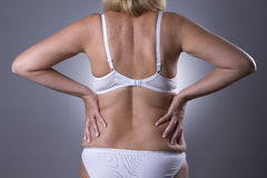 Back pain, kidney inflammation, ache in woman`s body. On gray background Royalty Free Stock Image