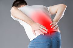 Back pain, kidney inflammation, man suffering from backache. Painful area highlighted in red royalty free stock images