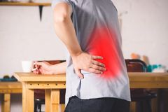 Back pain, kidney inflammation, man suffering from backache at home. Painful area highlighted in red royalty free stock photo