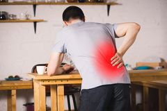 Back pain, kidney inflammation, man suffering from backache at home. Painful area highlighted in red royalty free stock image