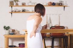 Back pain, kidney inflammation, woman suffering from backache at home. Painful area highlighted in red stock photo