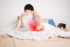 Back pain, kidney inflammation, woman suffering from backache at home. Painful area highlighted in red Stock Image