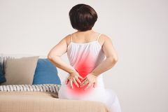 Back pain, kidney inflammation, woman suffering from backache at home. Painful area highlighted in red Stock Images