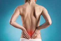 Back pain. Muscle cramp or backache on naked woman's back. Young female touching her painful back Stock Photography