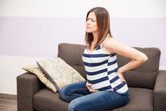 Back pain during pregnancy. Attractive young brunette feeling back pain during her pregnancy while resting at home Royalty Free Stock Images
