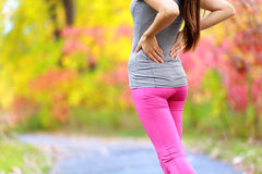 Back pain - running woman with back injury Royalty Free Stock Photo