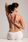 Back pain and stretch for semi nude young woman Royalty Free Stock Photography