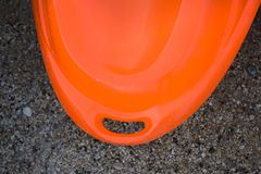 Back Part with Hole of Orange Kayak on Pebbled Land. Stern the Rear End of Water Boat. Outdoor Seasport and Adventure. Normal Wear and Tear on the Sides stock photos