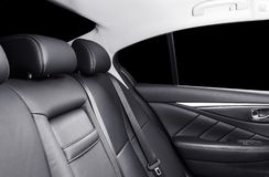 Back passenger seats in modern luxury car. Frontal view. Black perforated leather with white stitching. Car detailing. Leather com. Fortable black seats. Car stock photo