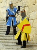 Back in the past. Men in historic costumes with swords behind bastion walls royalty free stock photography