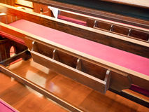Back of pew with bookshelf in empty church. Cathedral Interior w Stock Photo