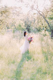 Back photo of the bride looking behind and holding the big bouquet of the flowers in the middle of the field. Royalty Free Stock Photo