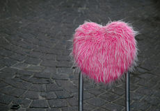 Back of pink chair in street. An unusual view of the back of a chair made of pink shaggy fabric in the shape of a heart or valentine Royalty Free Stock Image