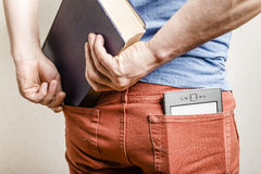 In the back pocket of jeans is an e-book, a man tries to shove in a second pocket paper book. In the back pocket of jeans is an e-book, a man tries to shove in a Royalty Free Stock Image