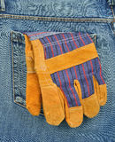 Back pocket of jeans with protective gloves Royalty Free Stock Photo