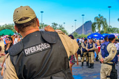 Back of the policeman taking pictures of costume people at Bloco Orquestra Voadora in Flamengo Park, Carnaval 2017 Royalty Free Stock Photos