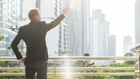 The back portrait silhouette smart business man stands with conf Stock Image