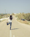Back portrait of single young girl jumping in the road Stock Photography