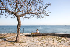 Back portrait woman sitting on a bench at the sea.amazing view,girl with curly hair,woman in white shirt,resting,spring holidays,s Royalty Free Stock Image